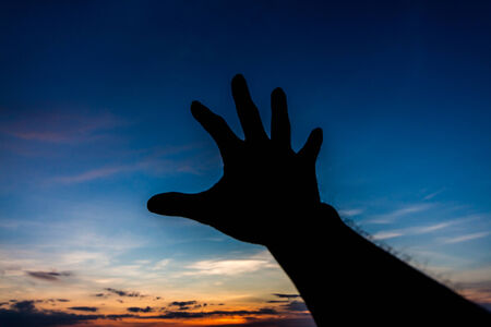 arm of a man: Hand try to reach something silhouette in sky