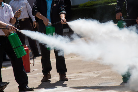 extinguisher: Instructor showing how to use a fire extinguisher on a training fire Stock Photo