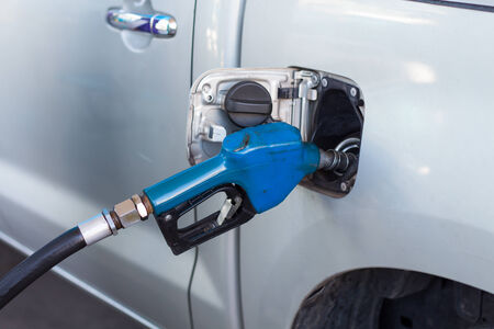 Car at gas station being filled with fuel photo