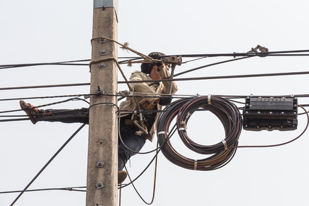 lineman: Electrician man work on electric pole for holding fiber optic cable