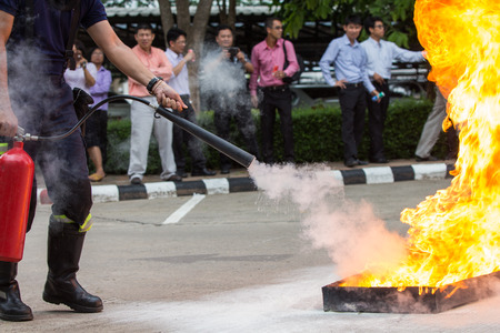 fire protection: Instructor showing how to use a fire extinguisher on a training fire Stock Photo