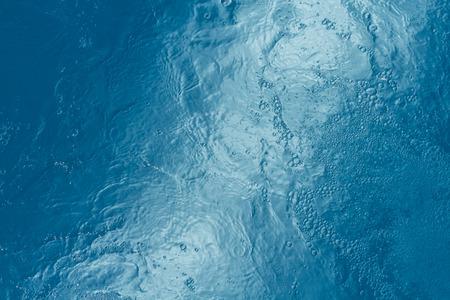 Mooi patroon van blauwe water weerspiegelt de zon.