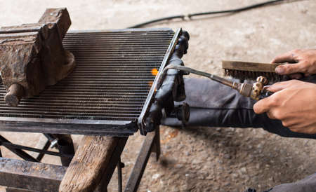 overheating: Technicians are welding for repair a leaking radiator. Stock Photo