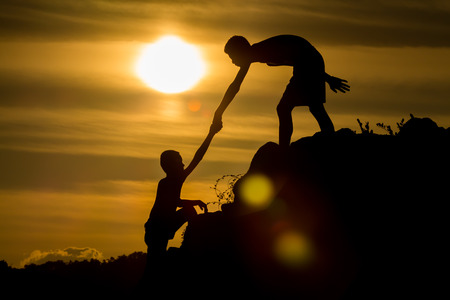 Silhouette of helping hand of a friend. Imagens