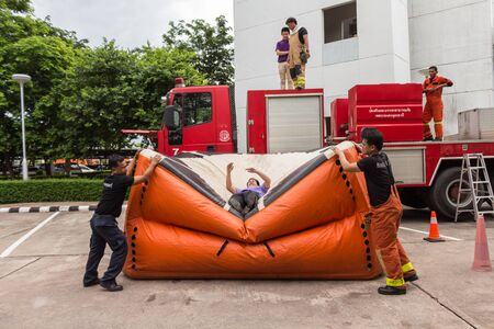 UDONTHANI, THAILAND - JULY 29, 2015:Firefighters teaching staff offices, jumping from a height into the safety air cushion in the annual fire training. Redakční