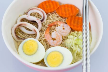 cooked instant noodle: Cook the noodles in a bowl.With condiments such as carrots, cabbage and seafood. Stock Photo