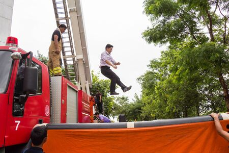 UDONTHANI, THAILAND - JULY 29, 2015:Firefighters teaching staff offices, jumping from a height into the safety air cushion in the annual fire training.