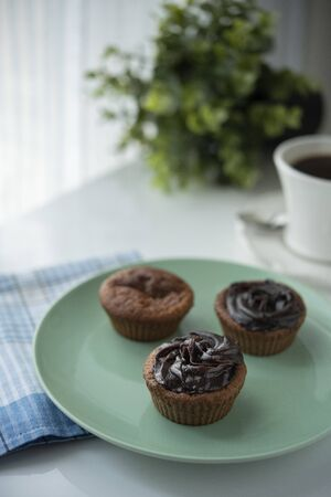 Chocolate muffin with coffee next to the window