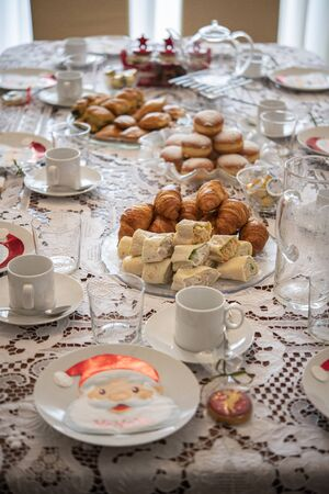 Christmas table with tortillas, croissant, cheese pie and santa claus napkins on plates