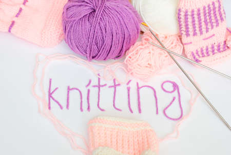 Written knitting with violet yarn, pink white and violet woolen skeins and knitted pieces  photo