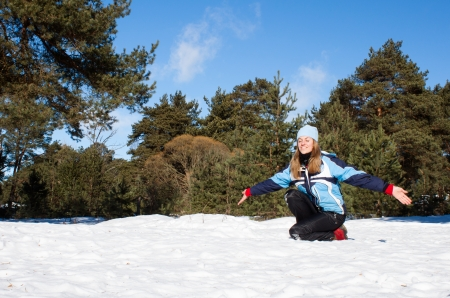 Young woman enjoying winter sun in a pine tree forest photo