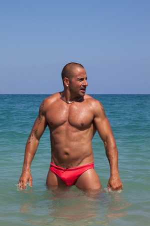Handsome man in a swimwear standing in the Mediterranean sea photo