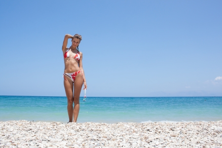 Young beautiful woman standing in the sea after swimming on the beach in Scopello, Sicily, Italy photo