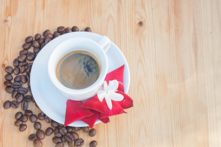 invigorate: Cup of coffee with coffee beans and rose petals on a wooden background