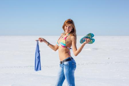 Beautiful woman in bikini and jeans enjoying hot spring sun near the frozen sea