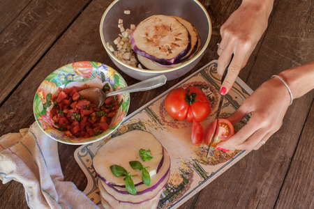 сooking: Hands ooking eggplants with tomatoes