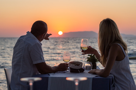 romantic beach: Couple relaxing in sea restaurant at sunset