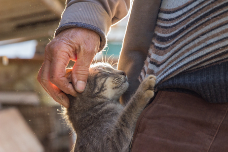 village man: Man with cat in village outdoors