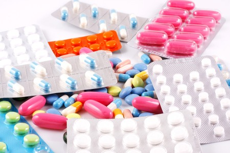 Pills of many shapes and colors grouped together photo