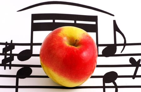Music notation elements and apple on white background Stock Photo - 7934377