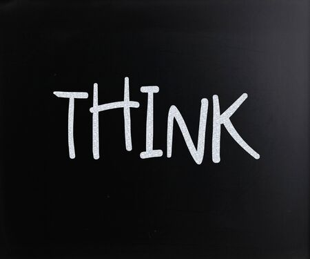 The word Think handwritten with white chalk on a blackboard photo