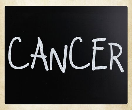 The word 'Cancer' handwritten with white chalk on a blackboard photo