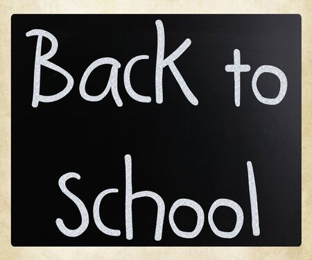 'Back to school' handwritten with white chalk on a blackboard photo