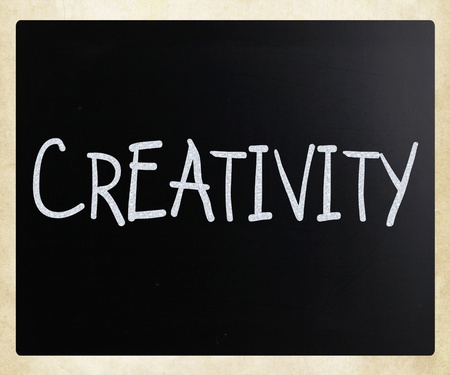 The word Creativity handwritten with white chalk on a blackboard photo