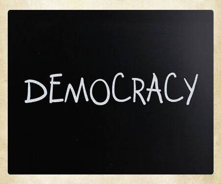 The word 'Democracy' handwritten with white chalk on a blackboard photo