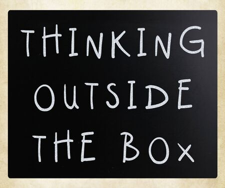 Thinking outside the box phrase, handwritten with white chalk on a blackboard photo