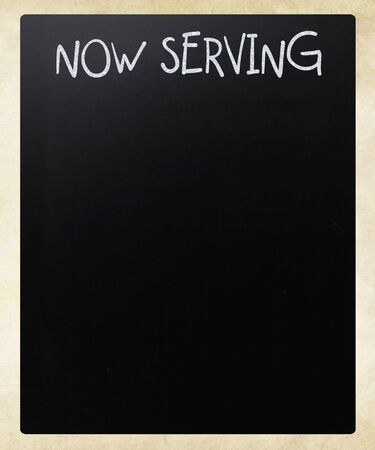 Now serving handwritten with white chalk on a blackboard photo
