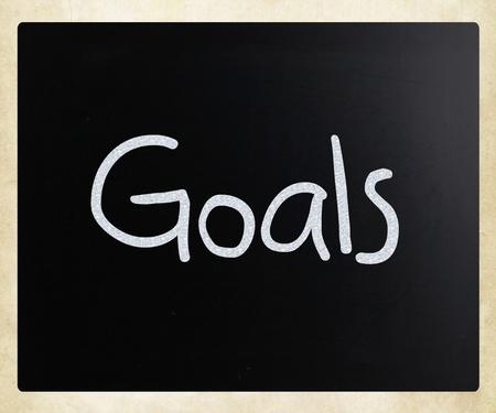 Goals handwritten with white chalk on a blackboard photo