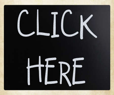 click here: Click here handwritten with white chalk on a blackboard Stock Photo