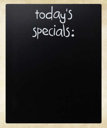 specials: Todays specials handwritten with white chalk on a blackboard Stock Photo