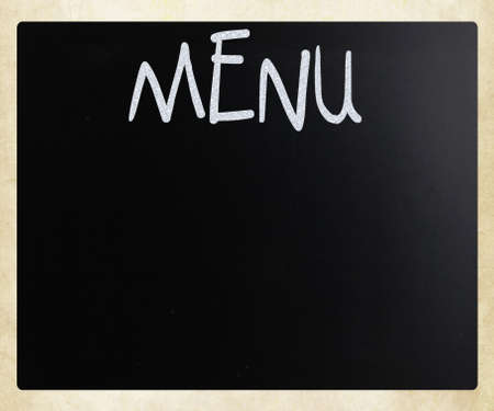 The word Menu handwritten with white chalk on a blackboard photo
