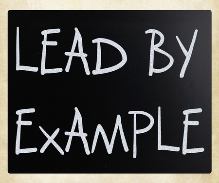 Lead by example handwritten with white chalk on a blackboard