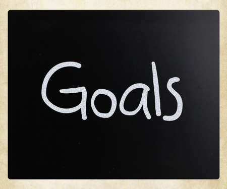 Goals handwritten with white chalk on a blackboard photo