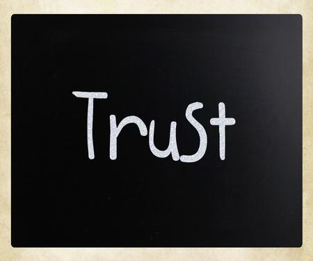 The word Trust handwritten with white chalk on a blackboard photo