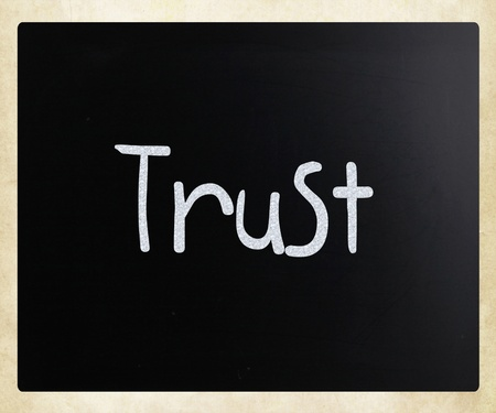 The word Trust handwritten with white chalk on a blackboard Stock Photo