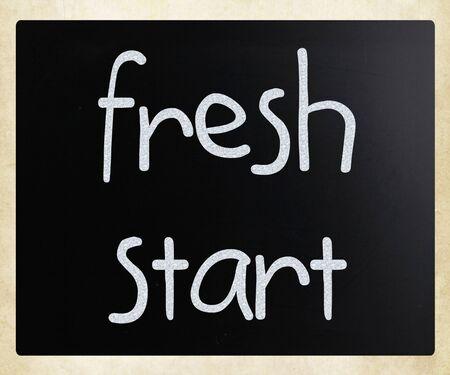 """frisse start: """"Nieuwe start"""" handgeschreven met wit krijt op een schoolbord Stockfoto"""