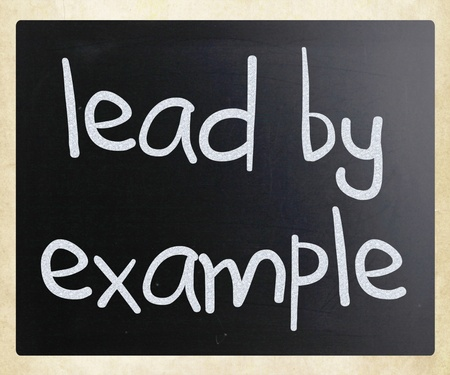 'Lead by example' handwritten with white chalk on a blackboard photo