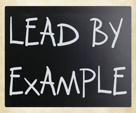 Lead by example handwritten with white chalk on a blackboard photo