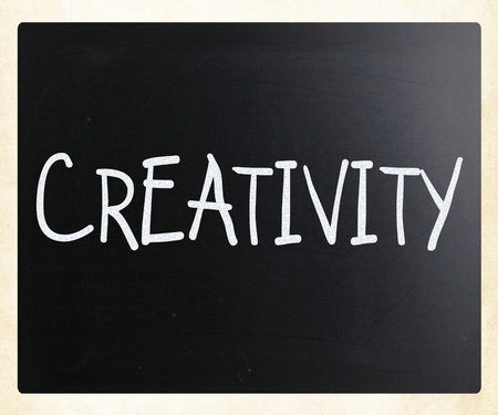 The word 'Creativity' handwritten with white chalk on a blackboard photo