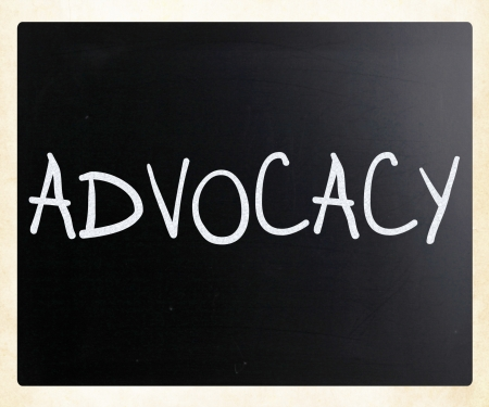 The word 'Advocacy' handwritten with white chalk on a blackboard photo