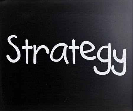 Strategy handwritten with white chalk on a blackboard photo
