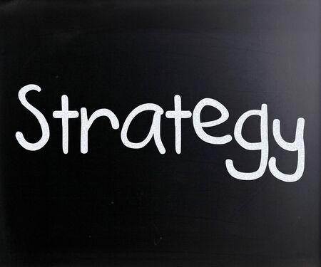 Strategy handwritten with white chalk on a blackboard photo