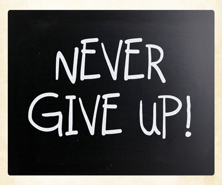 Never give up handwritten with white chalk on a blackboard