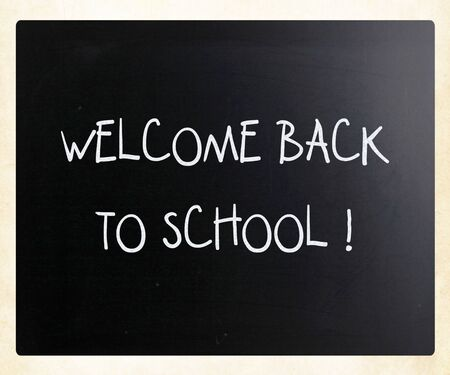 'Welcome back to school' handwritten with white chalk on a blackboard photo