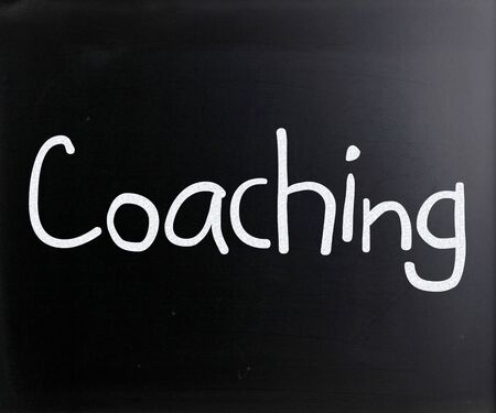 'Coaching' handwritten with white chalk on a blackboard photo