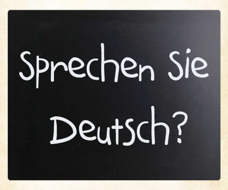 deutsch: Sprechen sie Deutsch handwritten with white chalk on a blackboard Stock Photo